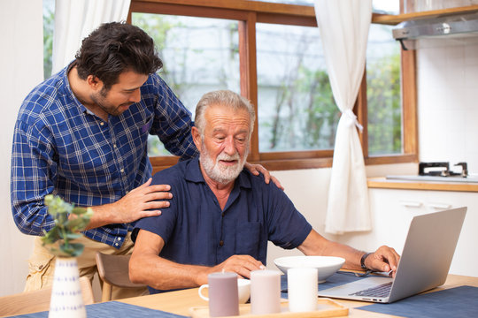Elder care in home, good mentor healthy smart old man using laptop computer stay at young man.