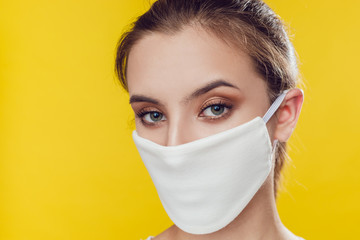 Woman wearing face protective mask on face against Coronavirus on the yellow background.