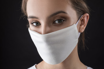 Woman wearing face protective mask on face against Coronavirus. COVID-19 Pandemic.