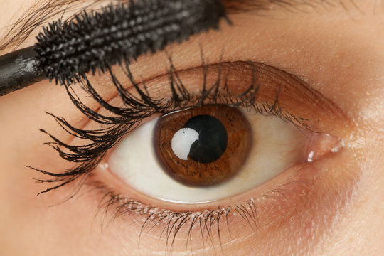 Close up view of a woman eye and mascara wand
