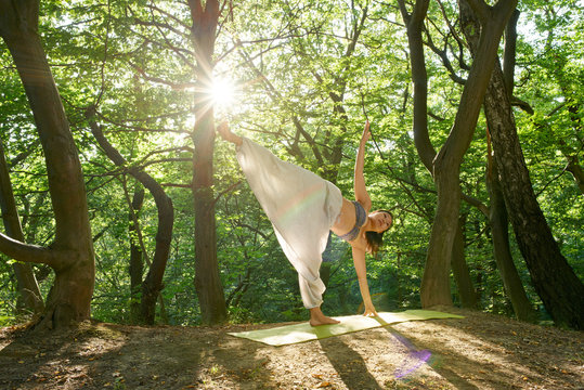 Yoga in natural Young yoga asian attractive woman practicing yoga concept, standing in Half Moon exercise, Ardha Chandrasana pose, working out, wearing sportswear Practicing yoga in nature at sunset