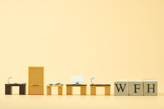 Miniature office table with wood block text of WFH.