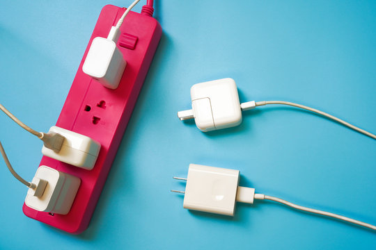 Pink extension power strip with only one socket left while there are 2 white mobile charger await to charge ,on blue pvc background ,strive for limited or shortage resource and competition concept