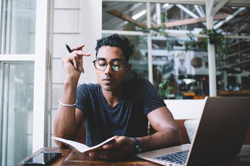 Thoughtful ethnic writer writing in journal while sitting at table with gadgets