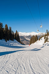 Fototapete - View of an alpine ski slope with cable car lift