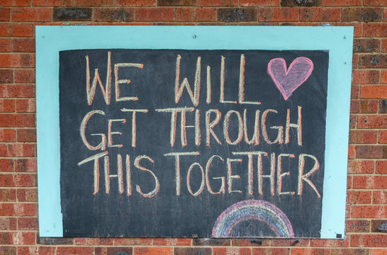 Chalk sign saying we will get through this together on a brick wall.  Written during the Coronavirus pandemic lockdown.