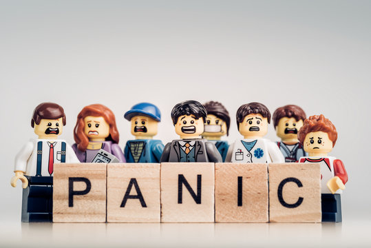Group of various panicking peopl with 'PANIC' sign