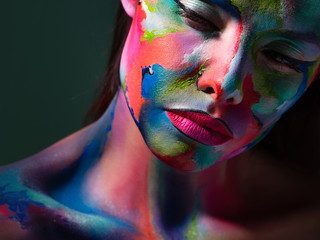 Face art and body art. Creative makeup with colorful patterns on the face. Modern makeup art, bold...