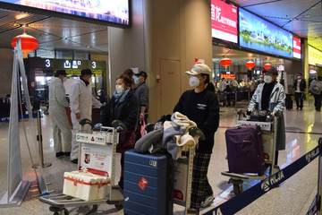 Passengers wearing face masks push luggage carts at an airport in Harbin, capital of Heilongjiang province bordering Russia, as the spread of the novel coronavirus disease (COVID-19) continues in the country