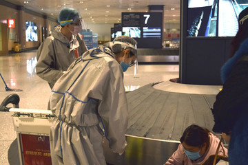 Airport workers in protective suits help a traveler look for her luggage at an airport in Harbin, capital of Heilongjiang province bordering Russia, as the spread of the novel coronavirus disease (COVID-19) continues in the country