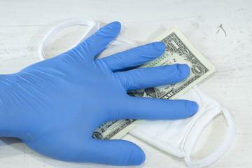 Obraz Ludzka ręka w niebieskiej rękawicy ochronnej trzymającej pakiet banknotów i maskę ochronną. - fototapety do salonu