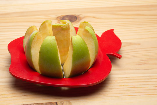 an Apple partially cut with an Apple cutter on a wooden background