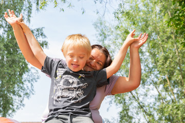 Happy mother and son with down syndrome playing together in a park.
