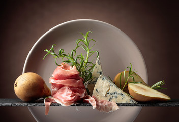 Wall Mural - Prosciutto or spanish jamon with blue cheese, pears and rosemary.