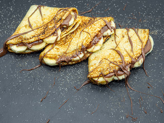 Fototapete - crepes with banana slices and chocolate served on slate