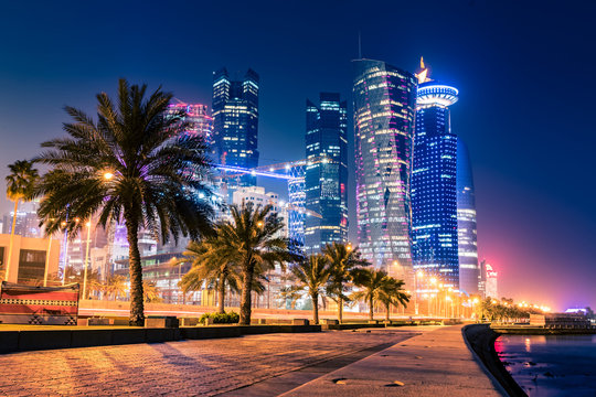 Night view on the centre of the city Doha, Qatar with many modern luxury building and skyscrapers illuminated with bright lights.