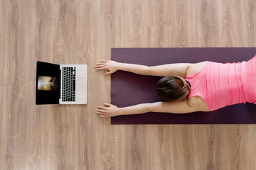 Attractive woman practicing yoga at home using online training instructions