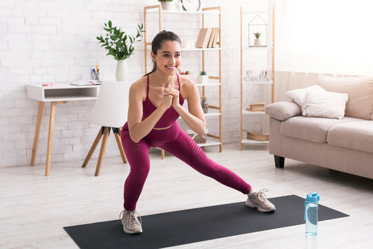 Stay home workout. Joyful millennial girl doing lunges on yoga mat in light room