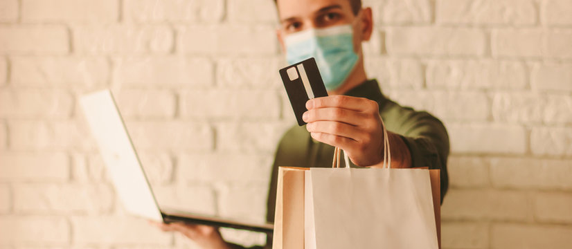 Happy hipster man in medical mask on face holding credit card, laptop and shopping bag in hands. Young man in protective face mask shopping online. Coronavirus COVID-19, internet payment, male shopper