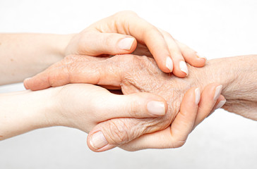 Helping hand for the elderly concept with young hands holding old hand.
