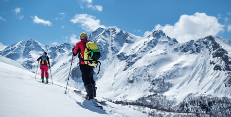 Two active men ski touring on mountain skis and splitboard at sunny winter day Wall mural