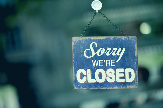 """Blue closed sign in the window of a shop displaying the message """"Sorry we are closed"""""""