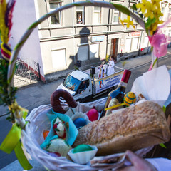 A priest sprinkles holy water on believers and their food during the celebrations of Holy Saturday in Bydgoszcz
