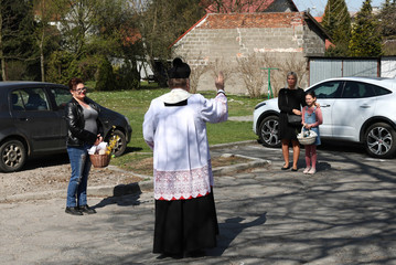 A priest sprinkles holy water on believers and their food during the celebrations of Holy Saturday in Niepolomice