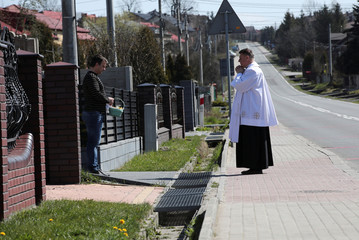 A priest sprinkles holy water on believers and their food during the celebrations of Holy Saturday in Olkusz