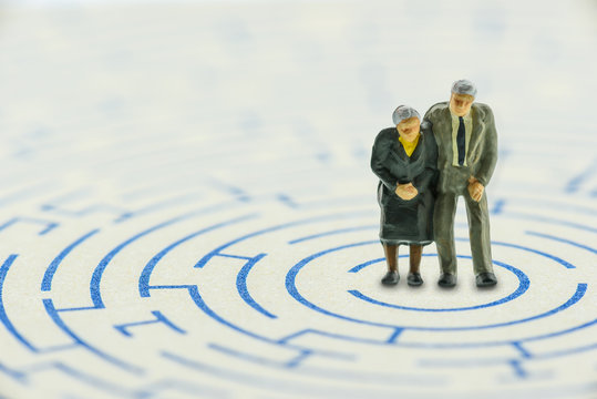 Senior couple in a complex maze try to find the way to escape
