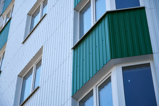 facade of a new multi-storey building with white and green metal siding, many Windows
