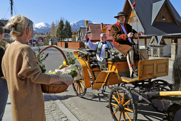 A priest sprinkles holy water on believers and their food during the celebrations of Holy Saturday in Zakopane