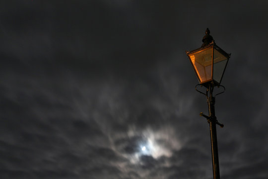 Unlit street lamp lantern with windy cloudy sky and moon