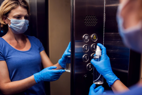 Woman with face medical mask and gloves doing disinfection of buttons in elevator. Hygiene and health protection concept