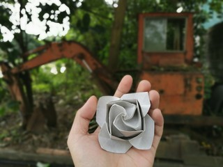 Cropped Hand Holding Paper Flower Against Earth Mover