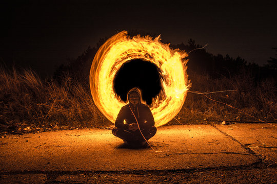Man Sitting Against Illuminated Wire Wool At Night