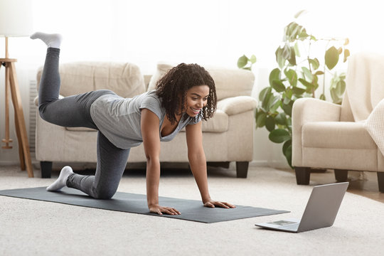 Fit Young Woman Excersising At Home, Watching Video Tutorial On Laptop