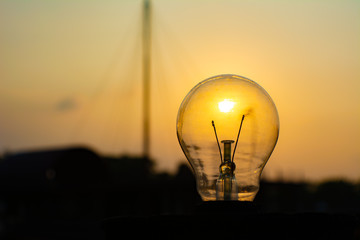 Close-up Of Light Bulb Against Silhouette Landscape During Sunset