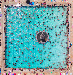 Aerial View Of People Enjoying At Poolside During Sunny Day