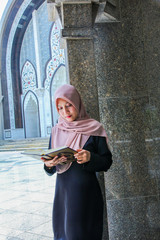 Young Woman Wearing Hijab While Reading Holy Book At Mosque