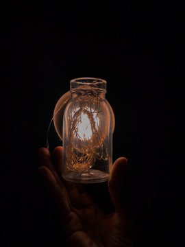 Cropped Hand Of Person Holding Glass Jar With Illuminated String Lights Against Black Background
