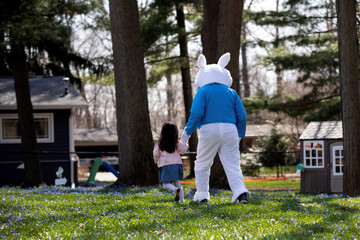 Genevieve Pina holds hands with a person dressed as an Easter bunny during a surprise visit to her house, amid the ongoing coronavirus disease (COVID-19) outbreak, in Plymouth, Michigan