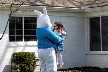 Genevieve Pina smiles as a person dressed as an Easter bunny surprises her and her brother in their backyard, amid the ongoing coronavirus disease (COVID-19) outbreak, in Plymouth, Michigan