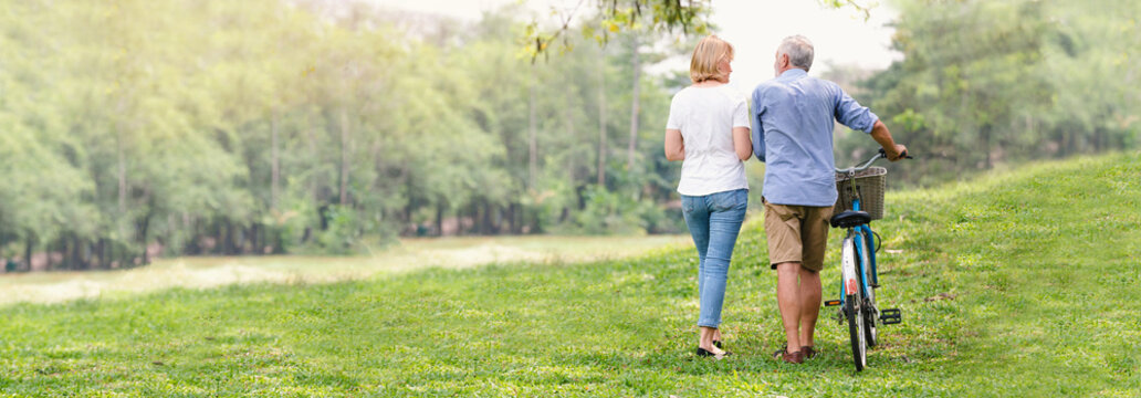 Elder healthy leisure lifestyle,Senior couple walking their bike along happily talking in the park, rear view of an older caucasian walk in a park, Banner image, Health care insurance