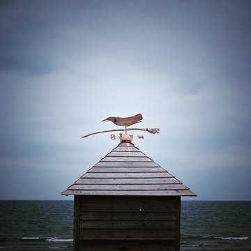 Weather Vane On Roof By Sea Against Sky