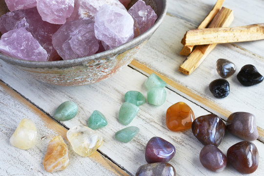 A top view image of rose quartz and various energy healing crystals on a white wooden table.