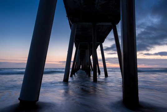 Long exposure of waves rushing in underneath the Hermosa Beach Pier just after sunset in Hermosa Beach, California.