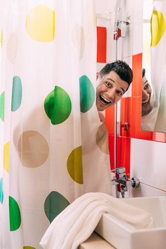 Portrait Of Happy Man Standing Behind Curtain At Bathroom