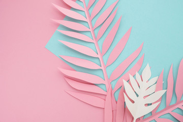 Tropical paper leaves on pastel background. Minimal bright summer composition. Top view, flat lay, copy space