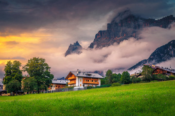 Wall Mural - Street view in the alpine village with misty mountains, Italy